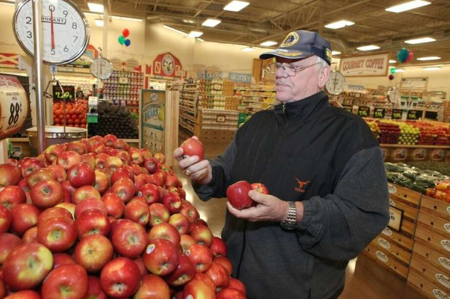 Jack Bierman of Katy looks over some apples at the grand opening of Sprouts Farmers Market in Katy. Photo: Alan Warren