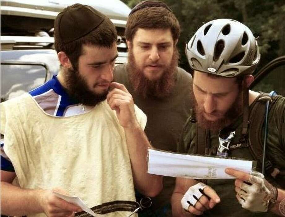 The three young rabbis on their cross-country friendship ride check directions along the way. Photo: Submitted Photo