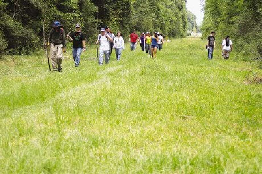 Searchers head back to their cars after looking for any sign of Amber Chantel Elkins near Greens Rd. and U.S. 59 on Friday, July 29. Photo: JASON FOCHTMAN