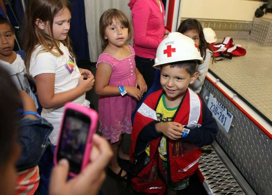 Micah Longoria, 4, tries out an American Red Cross outfit at the 2012 Hurricane Workshop at George R. Brown Convention Center Saturday. Photo: ALAN WARREN