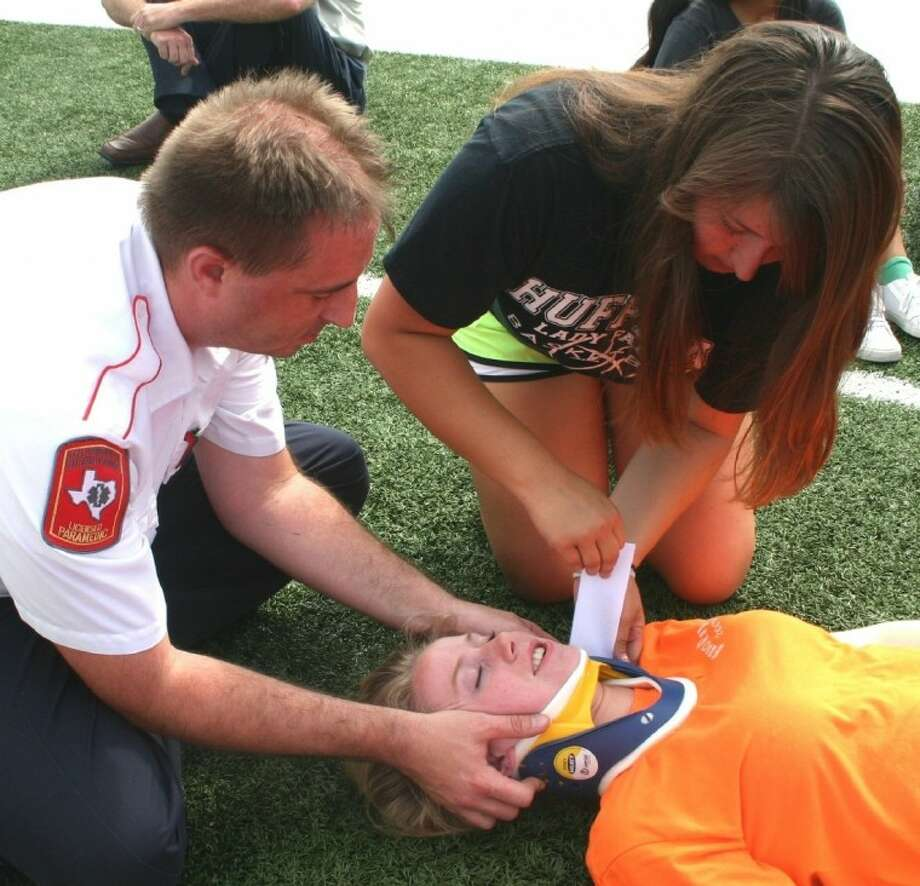 NorthStar EMS Operations Supervisor Heath Manson holds steady the head of an injured cheerleader, role played by Huffman Independent School District student athletic trainer Brittany Fields, while Fields' colleague, Rachel Bryan, applies a cervical collar. Thirteen students learned and practiced the fundamentals of handling certain emergecies, training that may be put to good use if EMS is en route. NorthStar and Huffman Volunteer Fire Department personnel, along with Athletic Trainer Riley Wheeler, conducted for 13 students the training exercises, which were held July 27 at the Hargrave High School football stadium. Photo: STEPHEN THOMAS