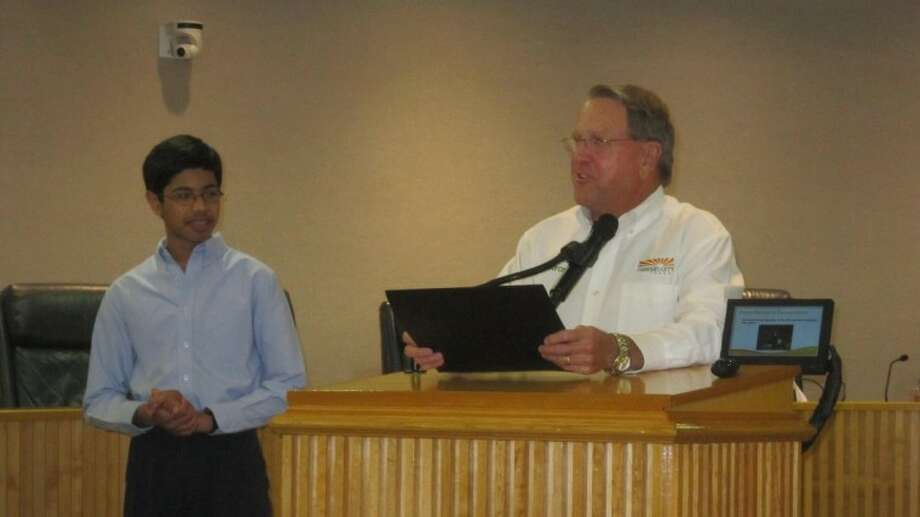 Fort Bend resident Rahul Nagvekar, left, is honored by Missouri City mayor Allen Owen and the City Council on June 4. Nagvekar won the National Geographic Bee.