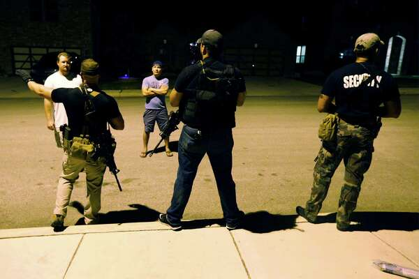 """For the past week, some residents openly carrying guns have patrolled their Cobblestone subdivision. Their shirts read """"security"""" so deputies and residents know they don't intend to be a menace."""