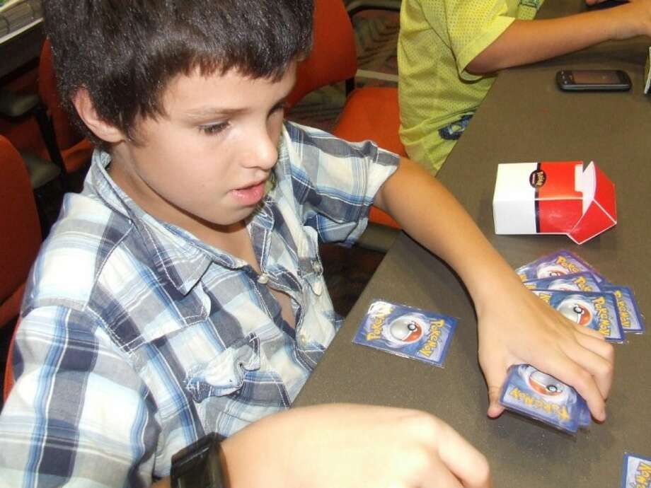 Corbin McDermott, 10, of The Woodlands, prepares his Pokémon cards as he begins a game at the Lone Star College - Tomball Library.