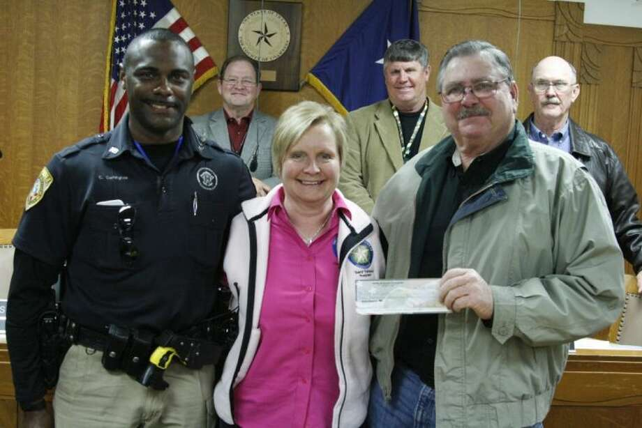 From left, Chambers County Deputy Carlton Carrington, Shane Detwiler Foundation founder and Shane Detwiler's mother Cheryl Railsback and Chambers County Commissioner Precinct 1 Mark Huddleston with Commissioners Rusty Senac, Gary Nelson and Bubba Abernathy in the background; accepted a check from the Shane Detwiler Foundation for the purchase of a new K-9 for the Chambers County Sheriff's Office.