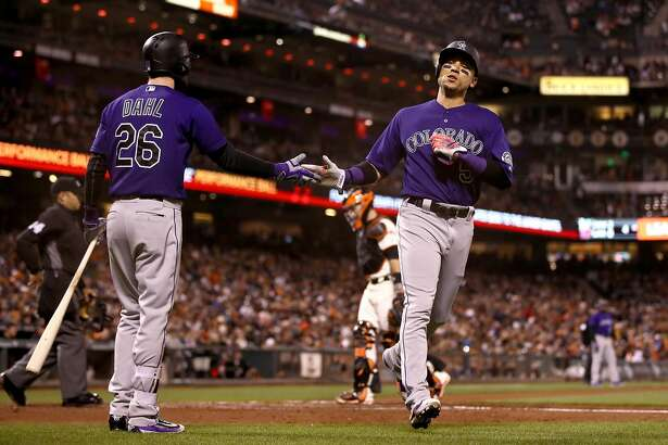 SAN FRANCISCO, CA - SEPTEMBER 28:  Carlos Gonzalez #5 of the Colorado Rockies is congratulated by David Dahl #26 after he scored on a single by Nolan Arenado #28 of the Colorado Rockies in the fourth inning at AT&T Park on September 28, 2016 in San Francisco, California.  (Photo by Ezra Shaw/Getty Images)