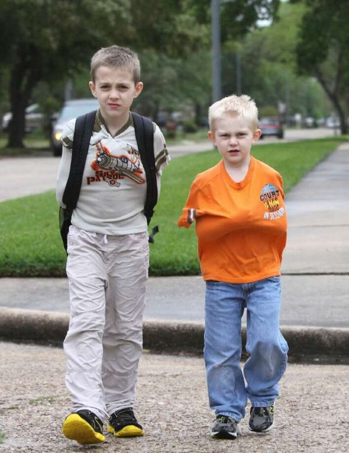 Thomas (l) and Jonathan Benn try to stay warm by keeping their arms inside their shirts as they walk home from school with their grandfather in Katy. A cold front moved through the Houston area this afternoon and dropped temperatures from the low 80's into the high 40's.