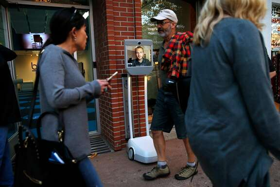 Salesperson Austen Trainer of Davis watches pedestrians walk by outside of Suitable Technologies' Beam store in Palo Alto, Calif., on Wednesday, September 28, 2016.