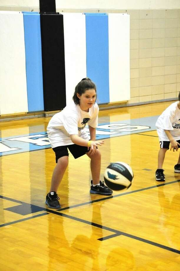 Eight-year-old Madison Ekstrom of Deer Park practices her basketball skills during the 2011 San Jacinto College basketball camp at the Central Campus. This year's camp is scheduled for July 23-27.