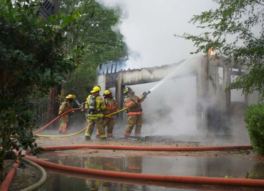 Firefighters with the Central Montgomery County Fire Department battle a residential fire off Stonewall Jackon Road in River Planation after Tuesday's storms passed.