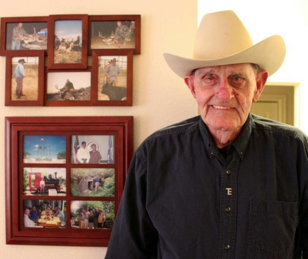 Tom Erskine at Parkway Place in front of pictures from deer hunting and his visit to Saipan in 2002.