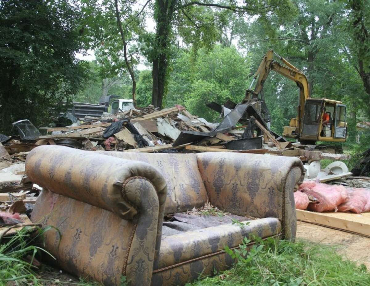 A dirty couch sits in the yard where a trailer house on Ross Ave. in Cleveland was demolished on Wednesday, June 20. The home is where several sexual assaults are alleged to have occurred in 2010 between an 11-year-old and multiple males.