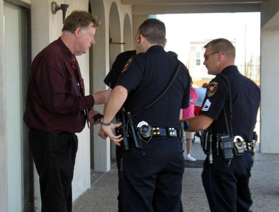 Chuck Fulner (left), CEO of Cleveland Regional Medical Center, is questioned by Capt. Scott Felts, Sgt. David Edwards and Officer Kevin Cooke regarding an alleged altercation that took place Wednesday, March 20, between Fulner and another hospital administrator. Photo: VANESA BRASHIER