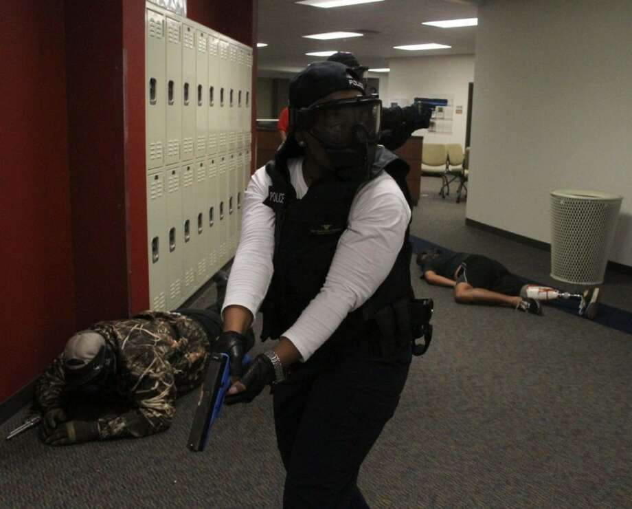 Marian Reed, a police officer with Rice University, takes part in a mock school shooting drill at Atascocita High School on July 12, 2012. Law enforcement personnel from all over the Houston and surrounding areas took part in the exercises designed to simulate a hostage event in a school setting. Photo: JASON FOCHTMAN