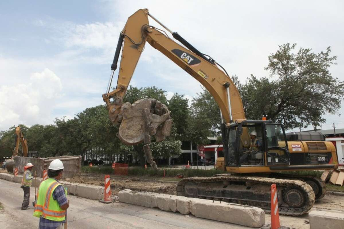 A backhoe loader removes sections of concrete along Richmond Avenue near Audley Street on July 3.