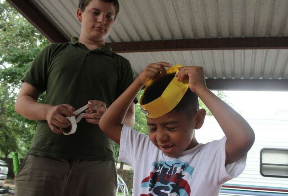 Jesus Garcia tries on his hand-crafted paper crown at a house on Campbell Acres off FM 2025 on July 11. The event, sponsored by Calvary Baptist Church, was part of the church's community service efforts around Cleveland, which included yard work and minor construction projects and holding the church's Backyard Bible Club meetings at businesses, residences and public parks. Photo: JASON FOCHTMAN