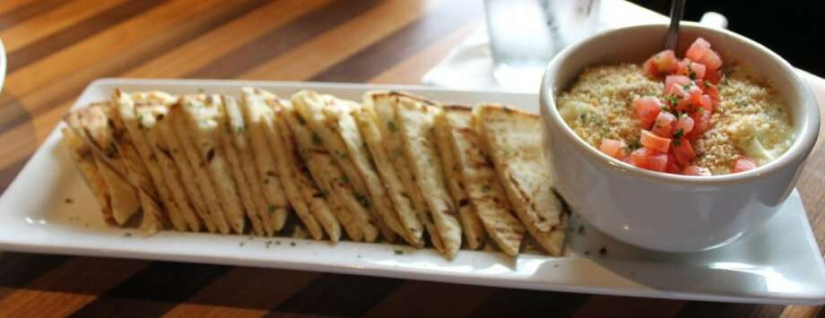 The Grille's spinach and artichoke dip from their appetizers menu. Sauteed spinach, prosciutto and artichoke hearts in a parmesan cream sauce topped with diced tomatoes and toasted bread crumbs, with grilled pita points.