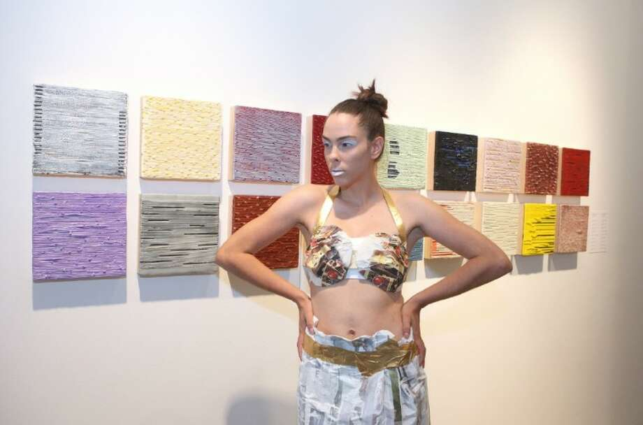 Model Michelle Carroll poses with clothes made from mixed-media, including vintage paper by Artist Deborah Porter next to artwork by Artist Winston Lee Mascarenhas. Porter partnered with Artist Zoe Jackson-Jarra of Fashion Plate Life Style Boutique for a fashion show in the Wade Wilson Art Gallery. Photo: Photo By Alan Warren