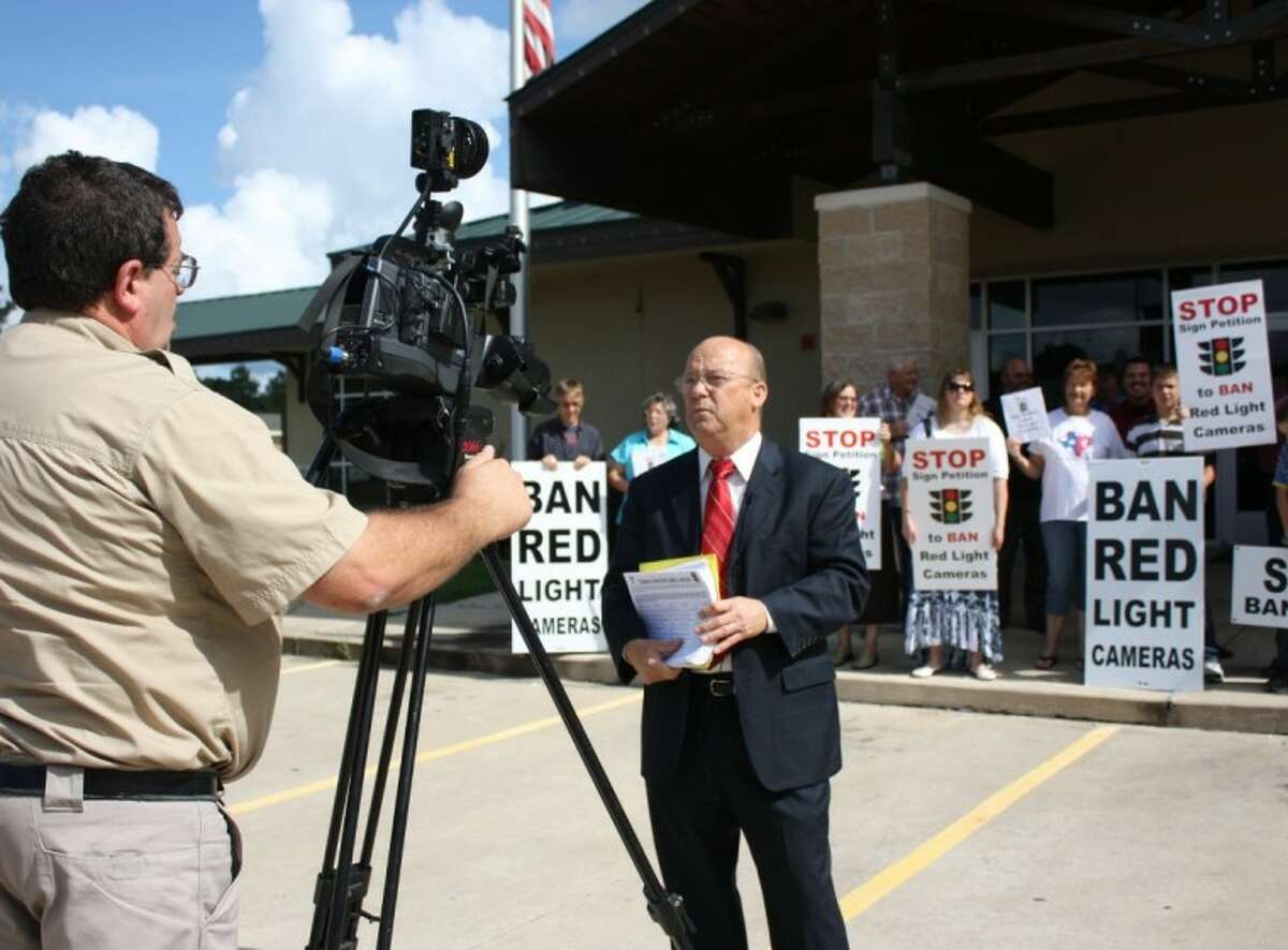 Aubrey Vaughan, center, of the Tri-County Texas Tea Party, is interviewed by television reporter Scott Engle, left, regarding the group's efforts to remove Cleveland's red light cameras. The group turned out on July 16 to turn in nearly 1,000 signatures of residents and nonresidents that signed a petition calling for the lights to be removed.