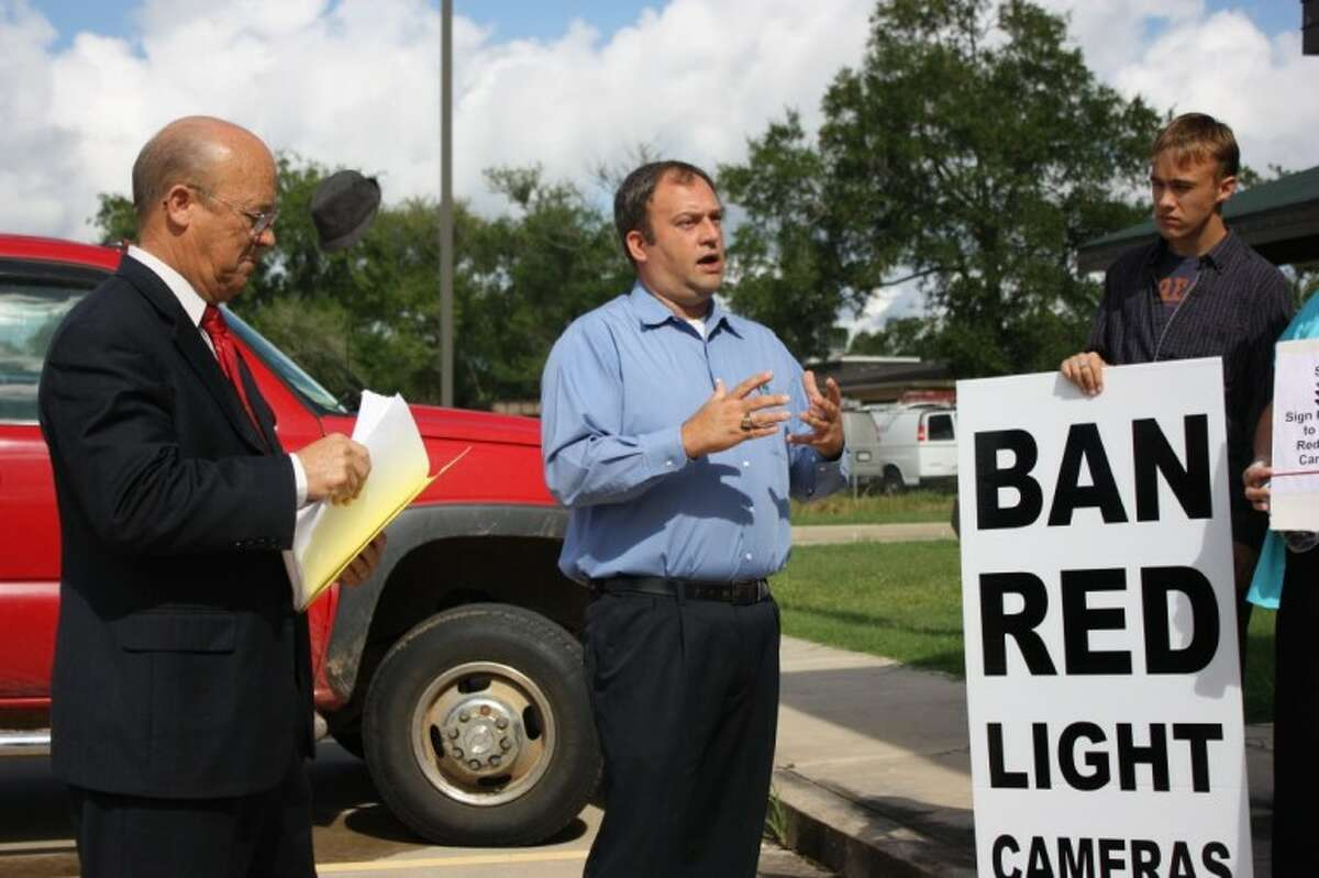 Byrom Schirmbeck, center, a Baytown resident that led that city's effort to remove their red light cameras, as been assisting the Tri-County Texas Tea Party in Cleveland. Shown on the left is Aubrey Vaughan.