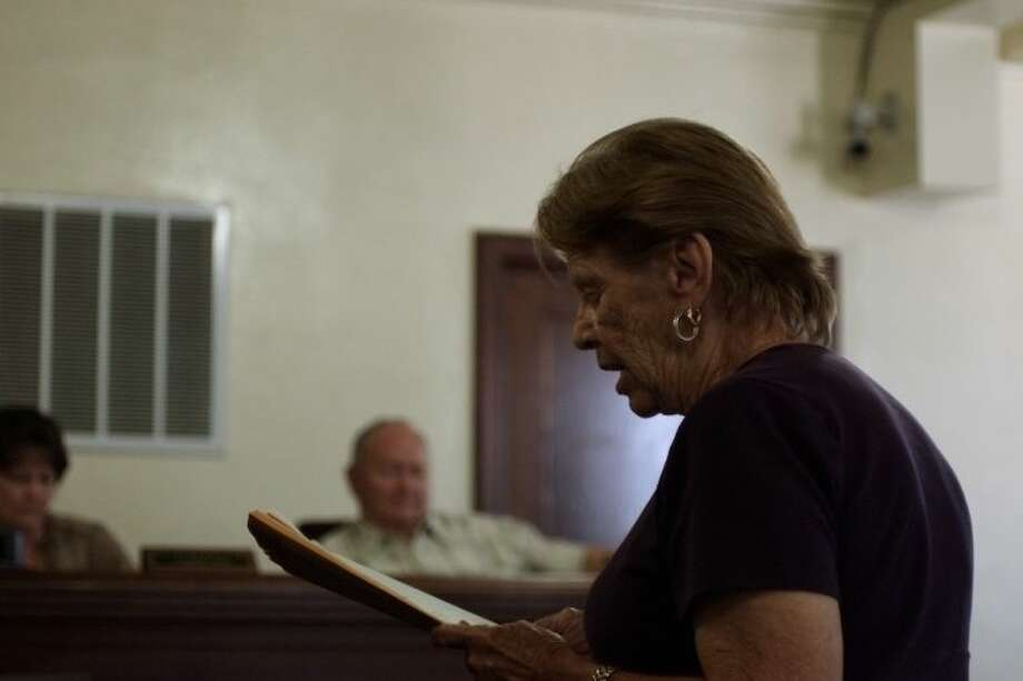 Kaye McCoy reads a statement to the commissioners regarding the county's tax on her property.