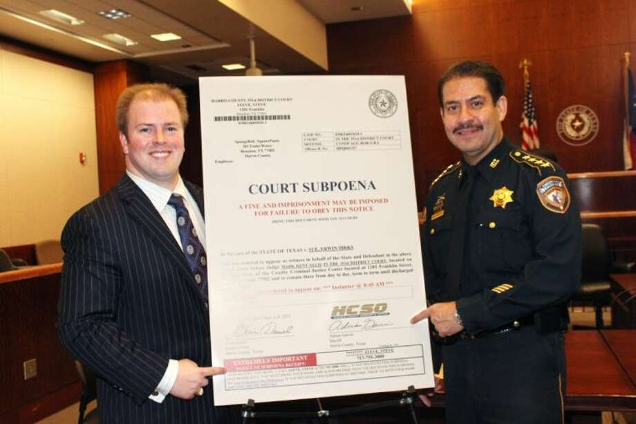District Clerk Chris Daniel, left, and Sheriff Adrian Garcia with a copy of the new subpoena.