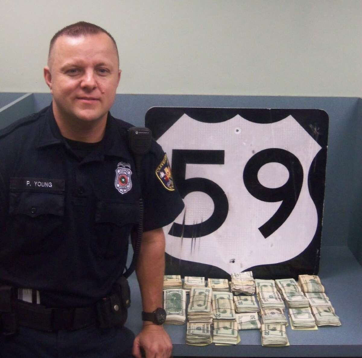 Cleveland Police Officer Paul Young displays the $30,000 in cash he seized Wednesday evening from a vehicle on US 59.
