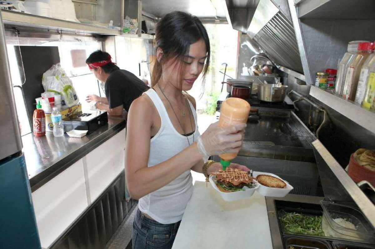 Nancy Luong of Kurbside Eatz puts finishing touches on a burger during lunchtime in Houston. Kurbside Eatz food truck will be a part of the Haute Wheels Houston Food Truck Festival March 22-23.