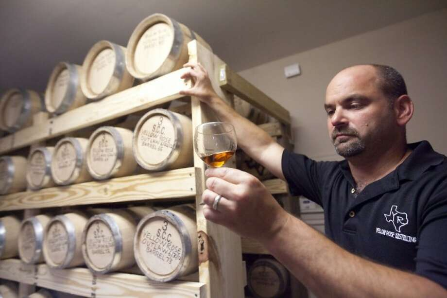 Troy Smith inspects whiskey in the aging room Yellow Rose Distilling in Pinehurst. Yellow Rose's new Outlaw Bourbon Whiskey will be availbale in area Spec's stores in mid-August. Photo: Karl Anderson