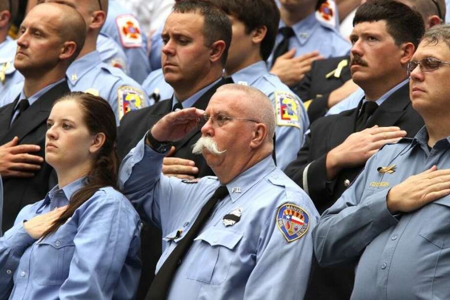 Firefighters salute during the national anthem at Wednesday's public memorial service for four fallen Houston firefighters.