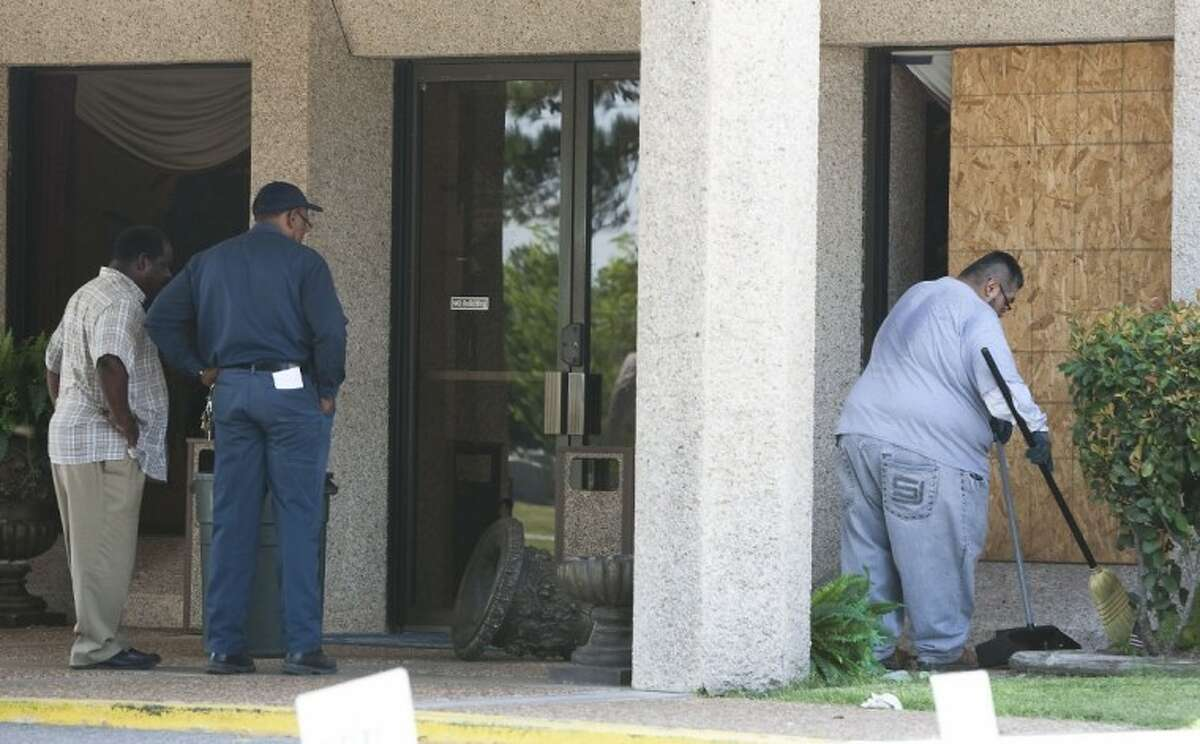 Maintenance workers clean up damage to Paradise Funeral Home in Houston after a mob of angry funeral attendees attacked Patrick Williams on Friday. Williams was later transported to a hospital where he died.