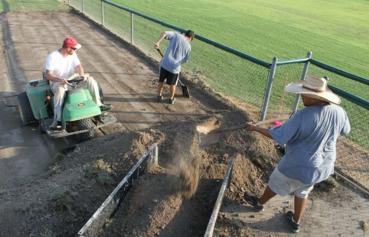 Humble Area Football League volunteers move and level dirt doing construction of an eating patio at Lindsey Lyons Park, using a tractor to use for hauling dirt instead of the customary utility vehicle stolen from HAFL's storage unit.