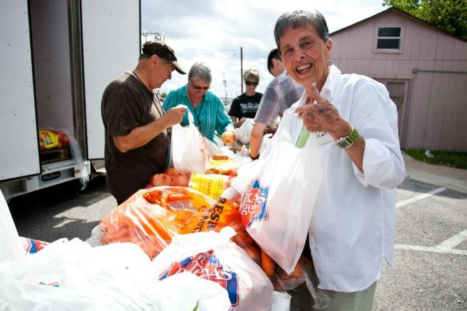 Anna Felts helps out with the Mobile Food Fair, held outside of the Humble Area Assistance Ministries May 30, 2013