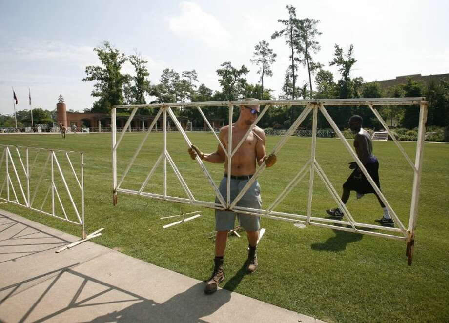 Michael Moyer puts barriers into place for the Ironman bike transition area at Town Green Park. Preparations are under way for the 2013 Ironman Texas to take place Saturday in The Woodlands.