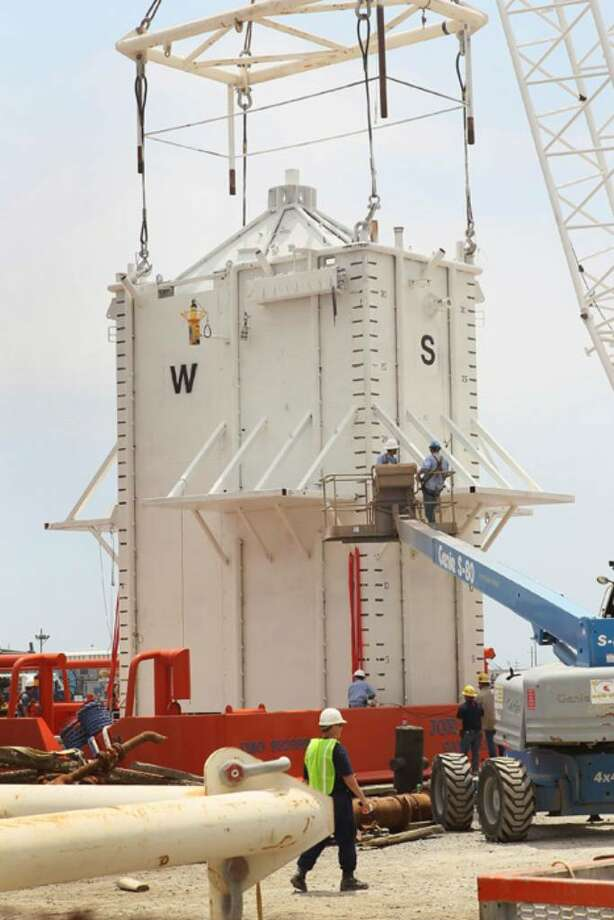 "PORT FOURCHON, LA - MAY 05:  A four-story 100-ton ""pollution control chamber"" which will be lowered 5,000 feet below the surface of the water to capture oil gushing from the collapsed oil well off the coast of Louisiana is loaded on the back of a ship  May 5, 2010 in Port Fourchon, Louisiana. The chamber, commissioned by BP, is planned to be lowered onto the leaking pipe by end of the week to try to suck in the flowing oil to tanker ship on the surface. The Deepwater Horizon offshore oil well began leaking after the rig caught fire and collapsed last month.  (Photo by Scott Olson/Getty Images) Photo: Scott Olson, Getty Images / 2010 Getty Images"