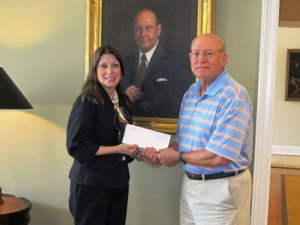 Diane Pavey, Girl Scouts of San Jacinto Council (GSSJC) major gifts director, receives a 100,000 gift from Buddy Zeagler, deputy executive director and controller for T.L.L. Temple Foundation, in front of a portrait of Arthur Temple, business man, philanthropist and the former chairman of the board of trustees for the T.L.L. Temple Foundation. The grant will go towards the construction of Camp Myra S. Pryor's Maime E. George Activity Center located near El Campo, Texas. Camp Pryor is one of eight GSSJC camp properties. It's eco-friendly design and river-side location makes it an ideal camp destination for girls in South Texas.