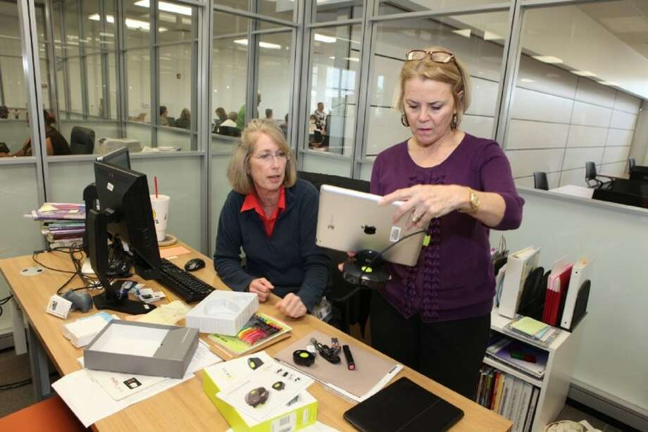 Karen Justi (left) and center director Sheri Alford look over a new Swivl, a personal cameraman device, to be used with an iPad by teachers in the classroom. Offices in the Technology Training Center are glass-walled for transparency and easy accessiblity to staff. Photo: Alan Warren