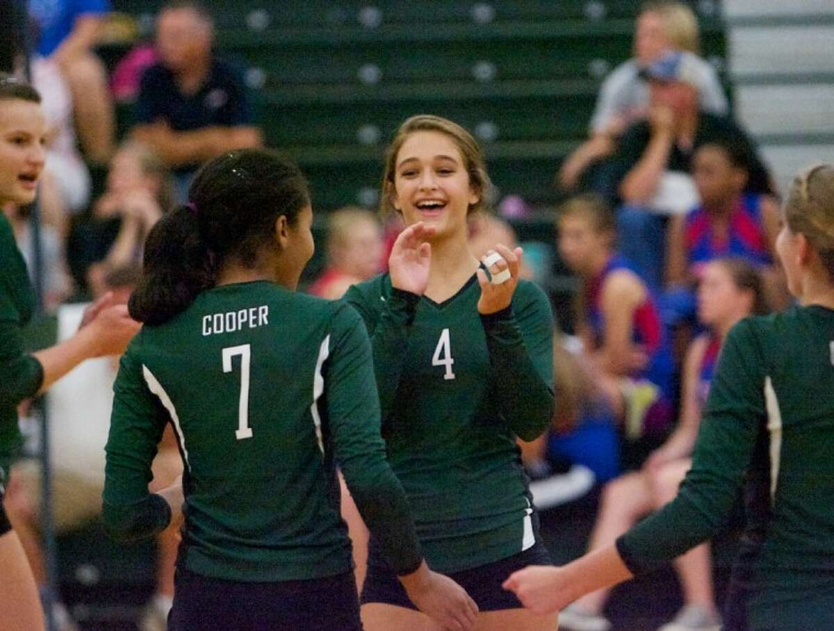 The John Cooper School's Christina Gooch celebrates a point with teammates during Wednesday night's season-opener against Lutheran North in The Woodlands.