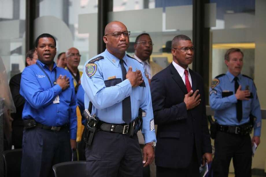 Houston Police Chief Charles McClelland and others listen to the National Anthem during a ceremony for National Police Week Day of Prayer in downtown Houston, Texas.