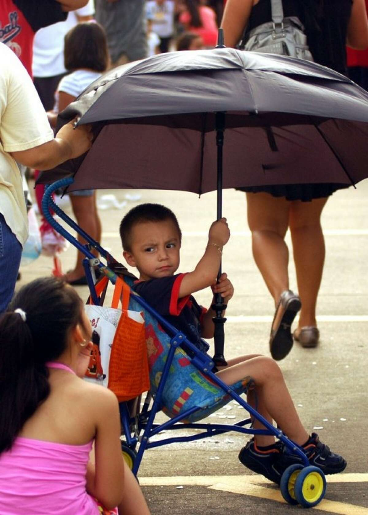 A youngster has both a seat and some shade Saturday while wating in line at the Back to School Health Fair at the Spring Branch Family Development Center.