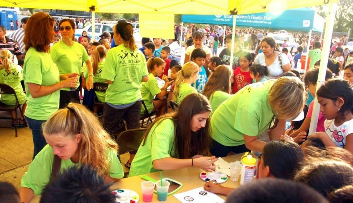 Mothers and daughters of the Memorial chapter of the National Charity League do face-painting Saturday's health fair..