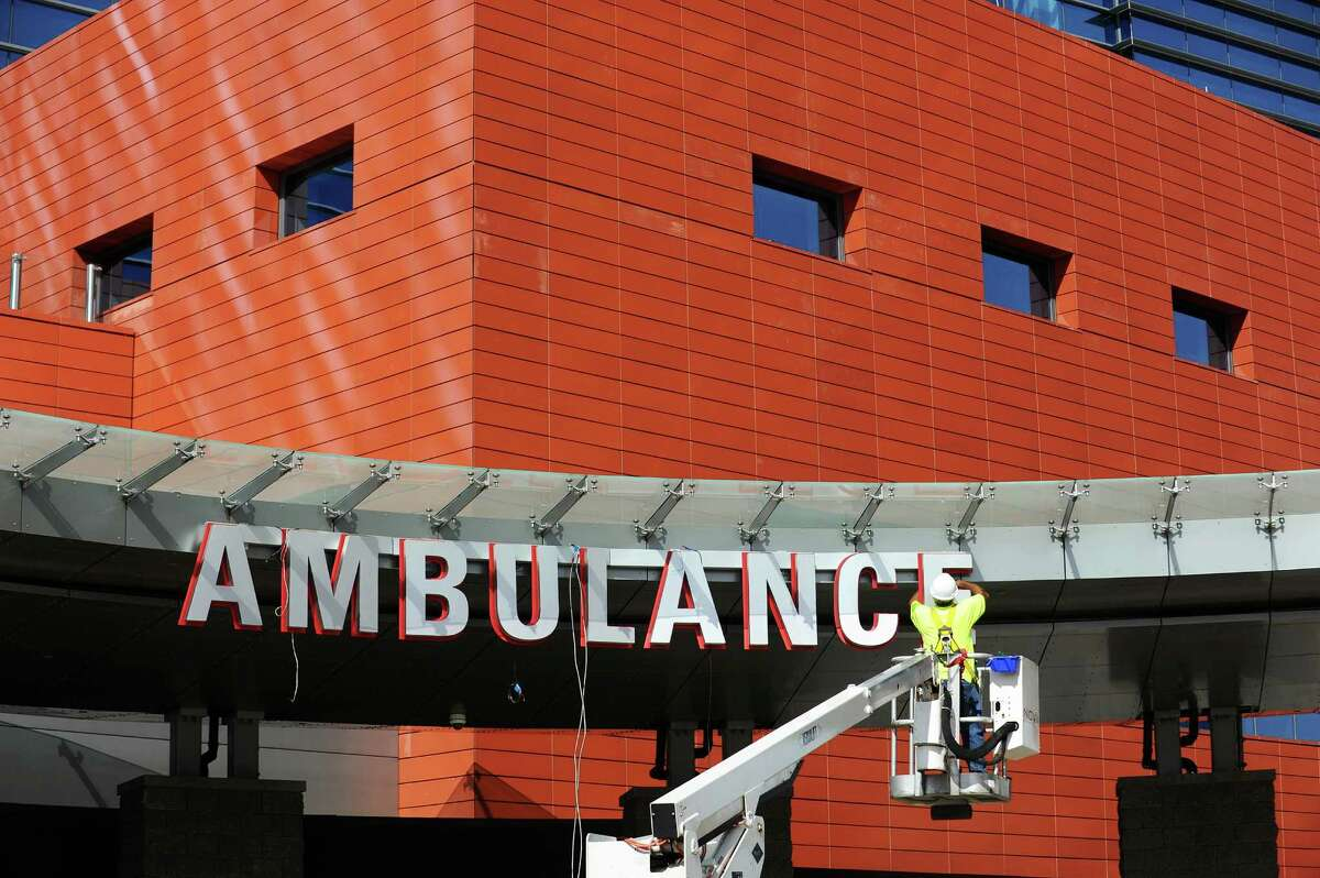 """In mid-September 2016, a worker finalizes the """"Ambulance"""" sign at Stamford Hospital in Stamford, Conn. On Sept. 27, the Connecticut Insurance Department revealed a proposed 10.9 percent reduction in the average loss costs charged by workers compensation insurers, a major component of overall workers comp rates."""