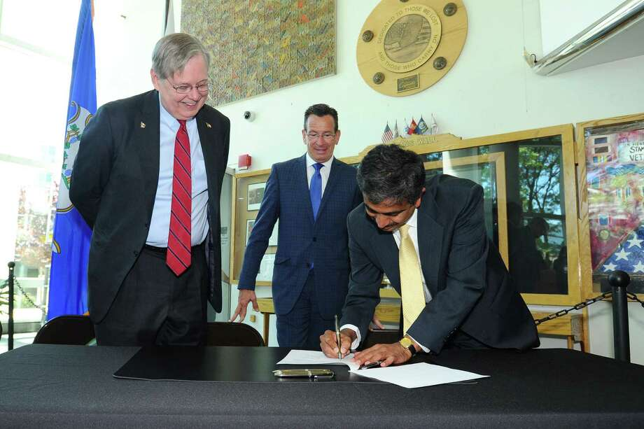 Tilak Subrahmanian, vice president of energy efficiency for Eversource, inks a partnership agreement in June 2016 with the city of Stamford accompanied by Mayor David Martin, left, and Connecticut Gov. Dannel P. Malloy. Photo: Michael Cummo / Hearst Connecticut Media / Stamford Advocate