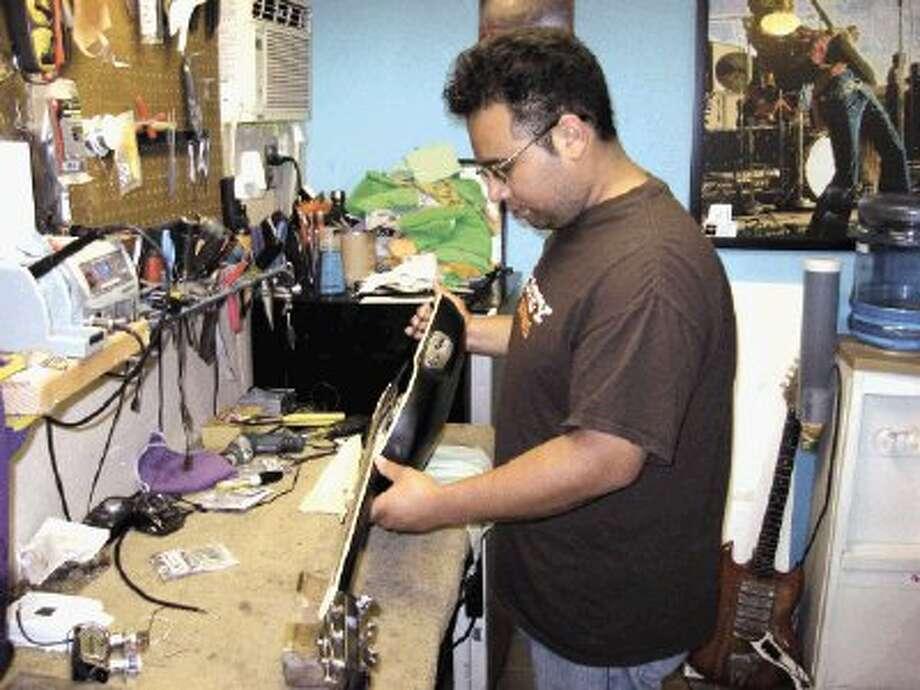 "daniel ""booney"" carranco checks the string action on an ovation guitar"