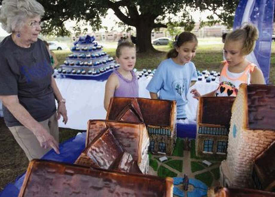 Julia Tiannotti, 10, left, Claire Franques, 9, center, and Sloan Starzyk, 10, get a closer look at an intricate cake by Celebrations and Sweet Creations during the groundbreaking Saturday for Frassati Catholic School in Spring. Photo: Staff Photo By Eric Swist