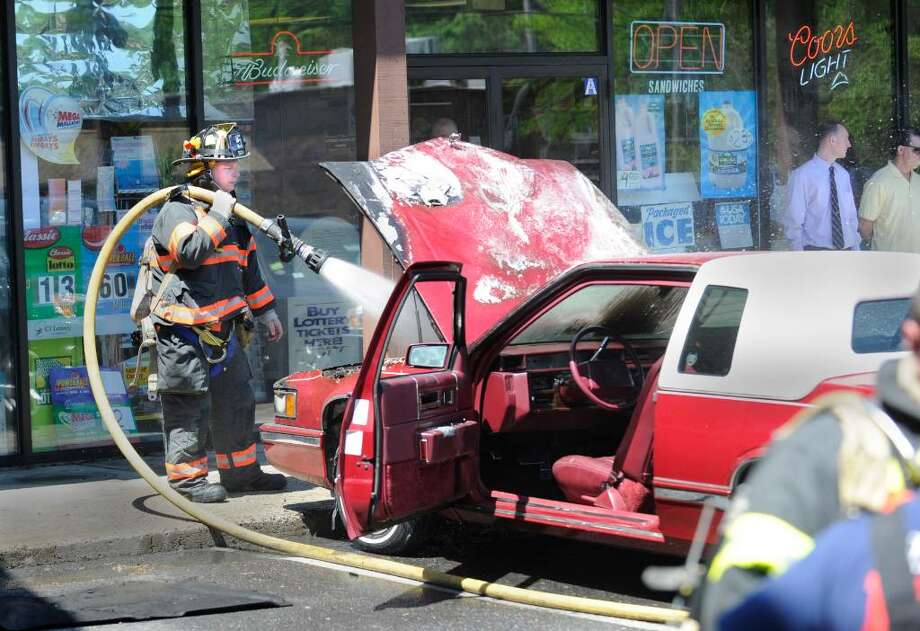 Sound Beach volunteer firefighter, Joe Gianfrancesco, douses a car with water, during the aftermath of a car fire in the parking lot of a small shopping plaza at 1345 East Putnam Avenue, Old Greenwich, early Wednesday afternoon, May 5, 2010. Photo: Bob Luckey / Greenwich Time