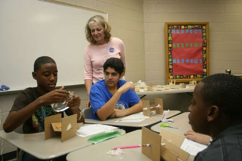 NASA Education Specialist Linda Smith watches as students take a closer look at rocks and sand from the surface of the moon. The students were participating in Summer of Innovation, a camp sponsored by NASA and the Galena Park ISD Scholars Academy.