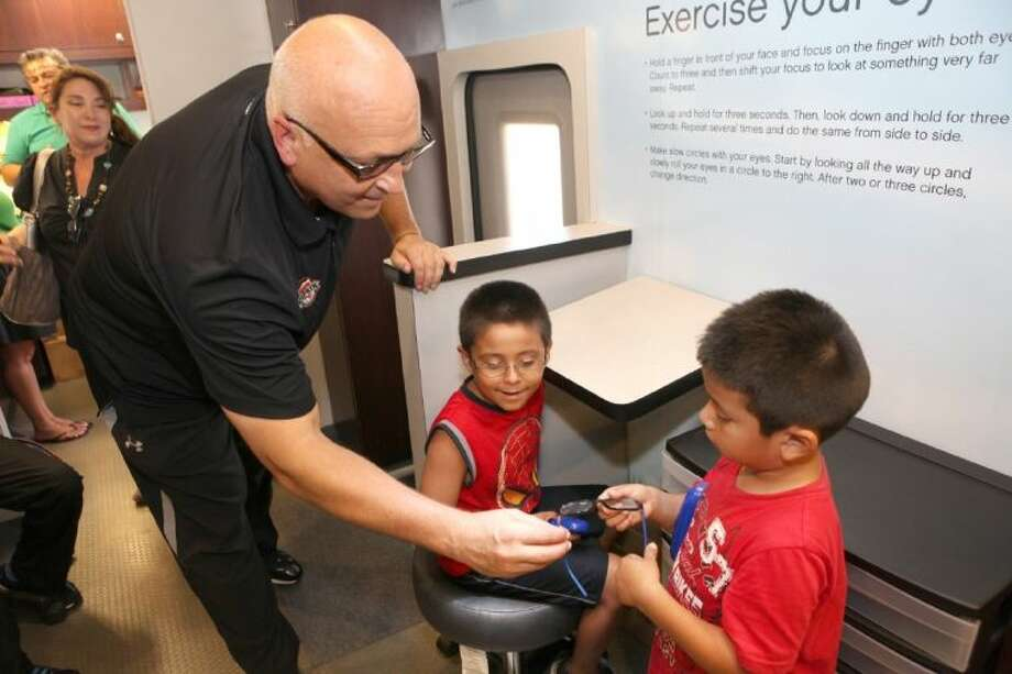 Major League Baseball Hall of Famer Cal Ripken, Jr looks at the new eyeglasses of David Espinosa, 6, (right) and Rodrigo Nambo, 7, last week in the Transitions Optical and VSP Vision Care Mobile Eye Clinic outside the Boys & Girls Club at the Spring Branch Family Development Center. Children at the Spring Branch Boys & Girls Club and SpringSpirit Baseball organization participated in a sports vision clinic with Ripken, Jr. that included a free comprehensive eye exam by a local VSP optometrist and free eyeglasses fitted with Transitions adaptive lenses for those children who need them, followed by a baseball clinic. Photo: Alan Warren