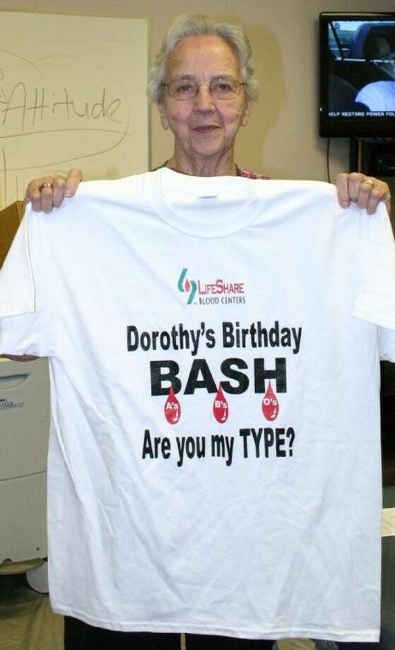 Dorothy Nettles shows the free T-shirt that each donor will receive at her Birthday Bash, which includes a LifeShare Blood Drive and a Health Fair at which flu and pneumonia shots will be given. The event was tentatively slated to be held from 2 p.m. to 7 p.m. on Friday, Sept. 7, at the First Baptist Church Gym in Dayton, but www.yourdaytonnews.com will post the new time and place if they change. Nettles, the LifeShare community liaison, will be 79. Photo: STEPHEN THOMAS