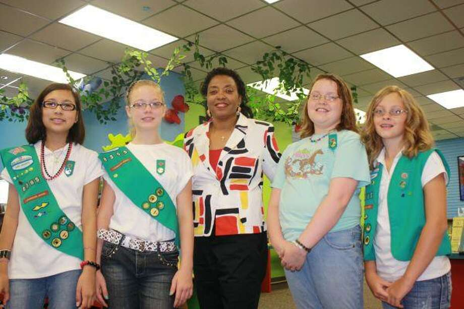 Members of the Junior Girl Scouts Troop No. 8365 pose with Library Director Sheila Henderson after the presentation.